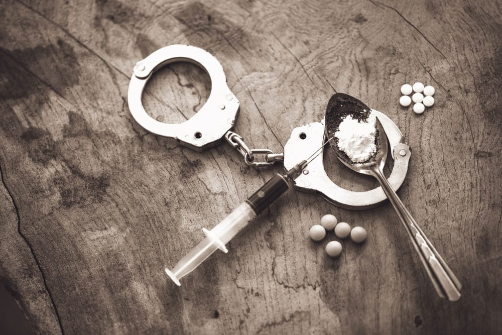 Syringe, heroin, and pills laying on top of handcuffs.